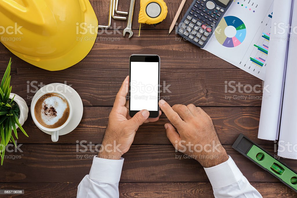 engineering using phone on his workspace top view stock photo