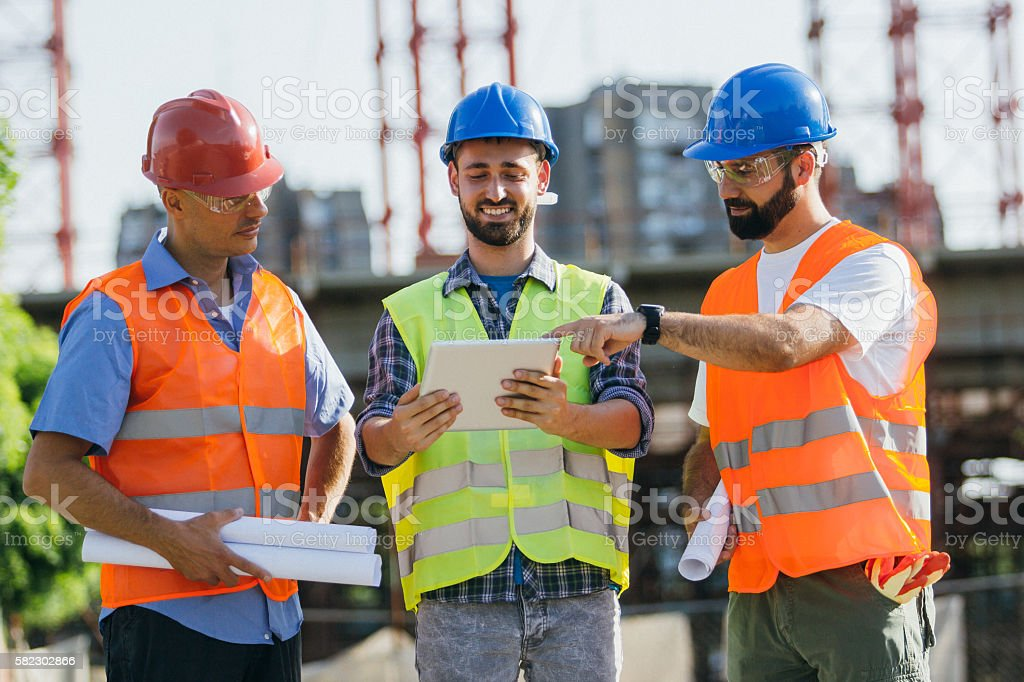 Engineers and architect making a project on construction site stock photo