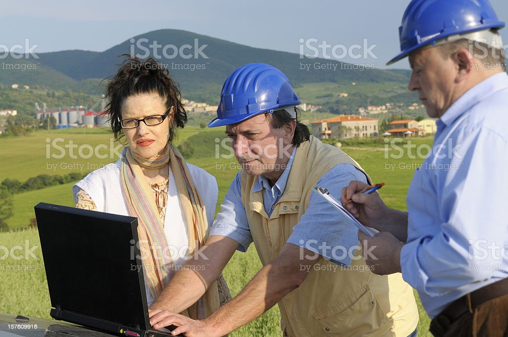 Engineers and Customer with Laptop in the Countryside royalty-free stock photo