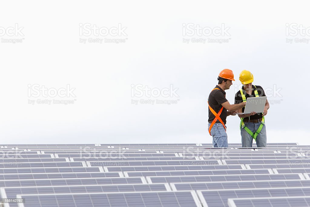 Engineers at a photovoltaic farm royalty-free stock photo