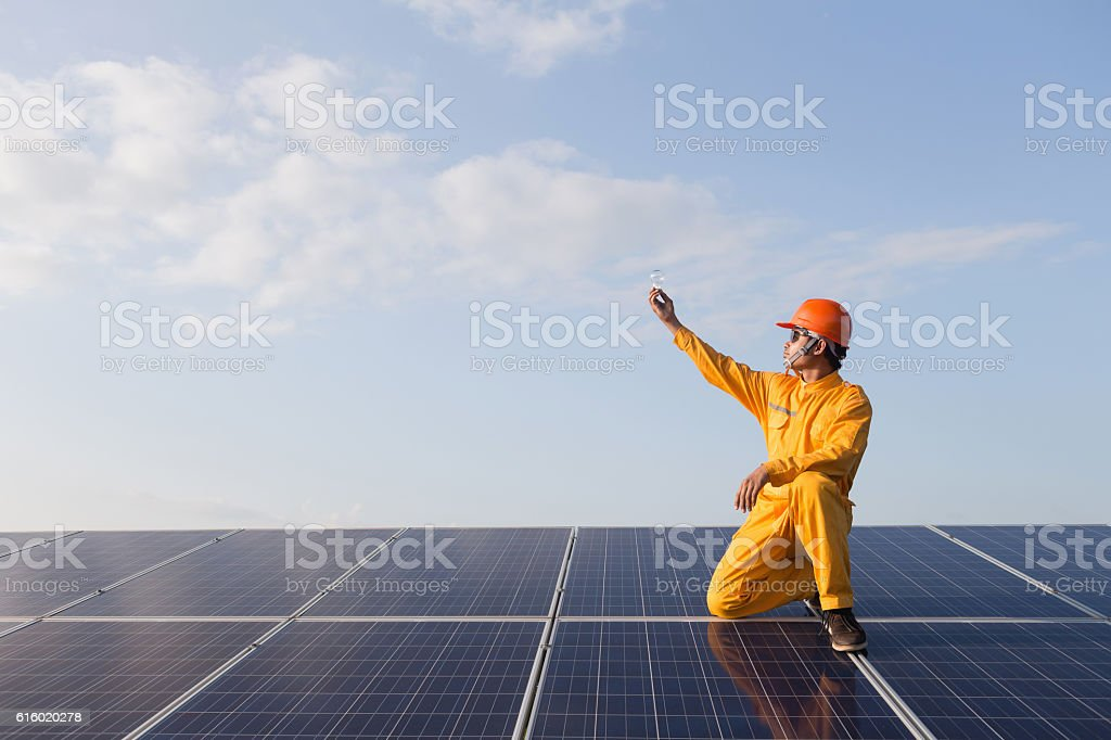 Engineers checking solar panels,Holding the bulb on stock photo