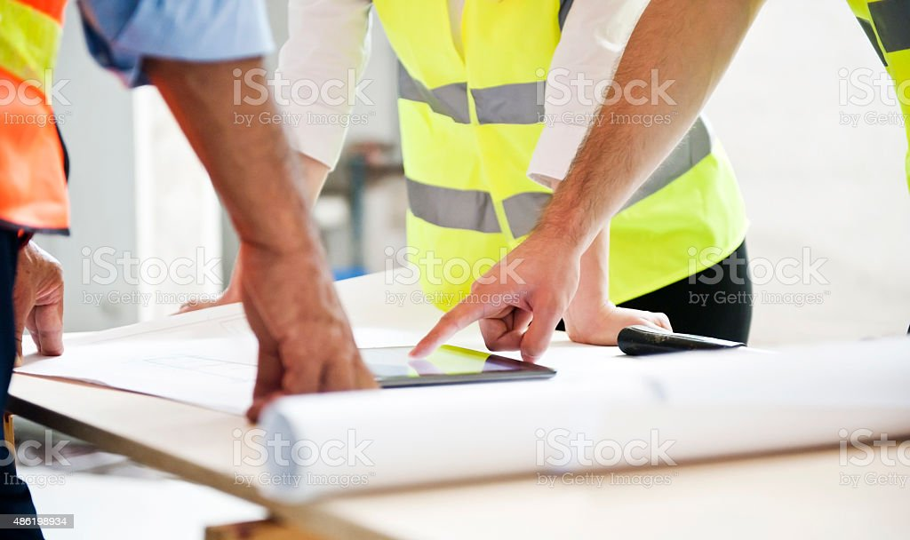 Engineers Examining Blueprint At Desk stock photo