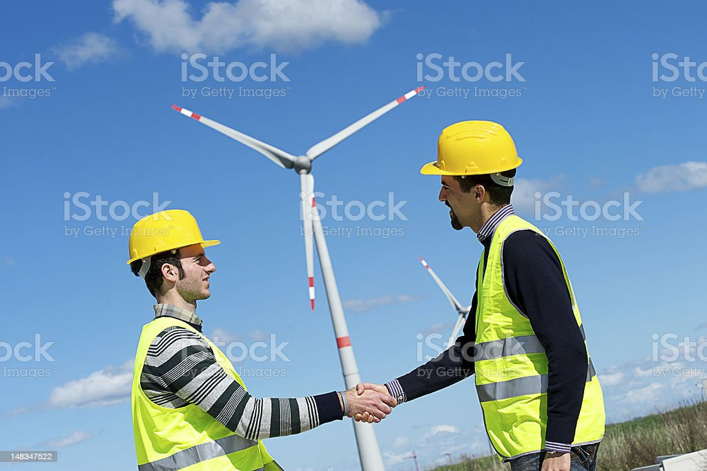 Engineers giving Handshake in a Wind Turbine Power Station royalty-free stock photo