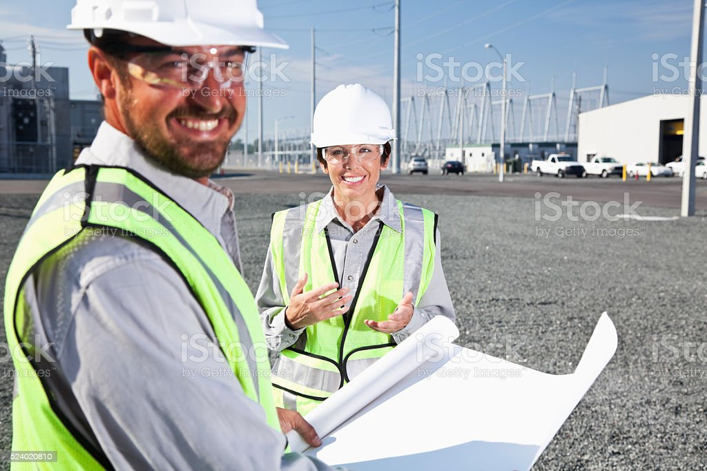 Engineers holding plans surveying power station stock photo