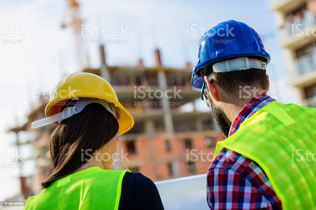Engineers looking at blueprints at construction site stock photo