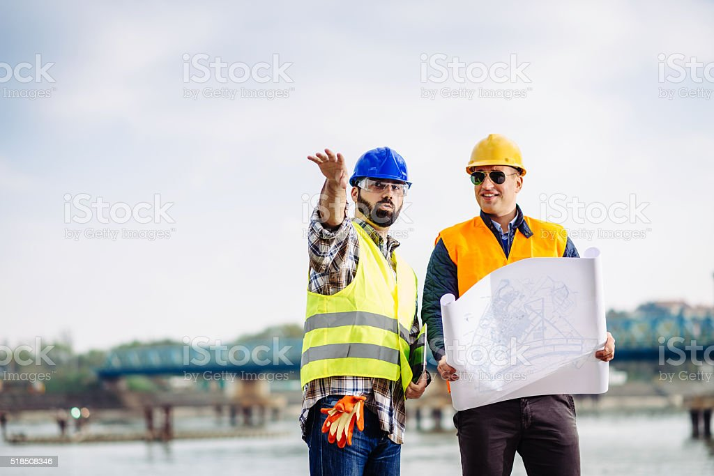 Engineers on bridge building site discussing next implementation phase stock photo