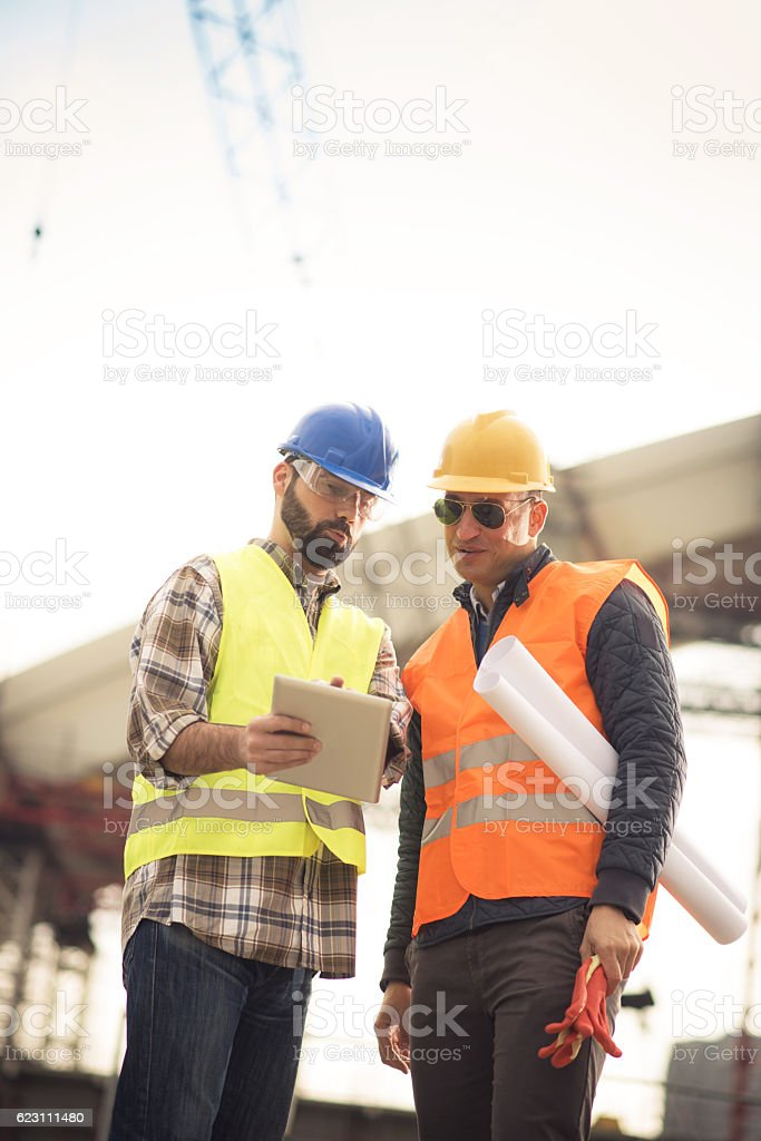 Engineers on construction platform with blueprints stock photo
