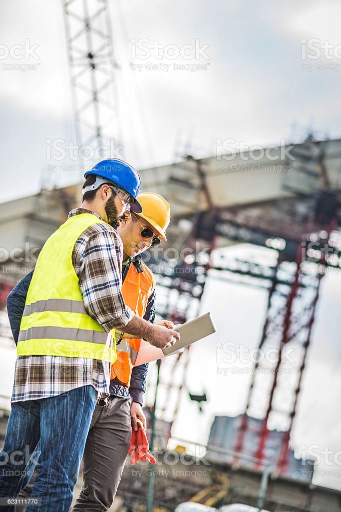 Engineers on construction site with crane and concrete frame stock photo