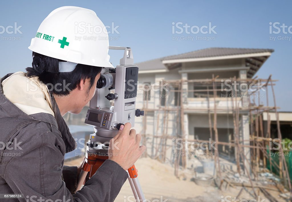Engineers use tacheometer or theodolite with house construction stock photo