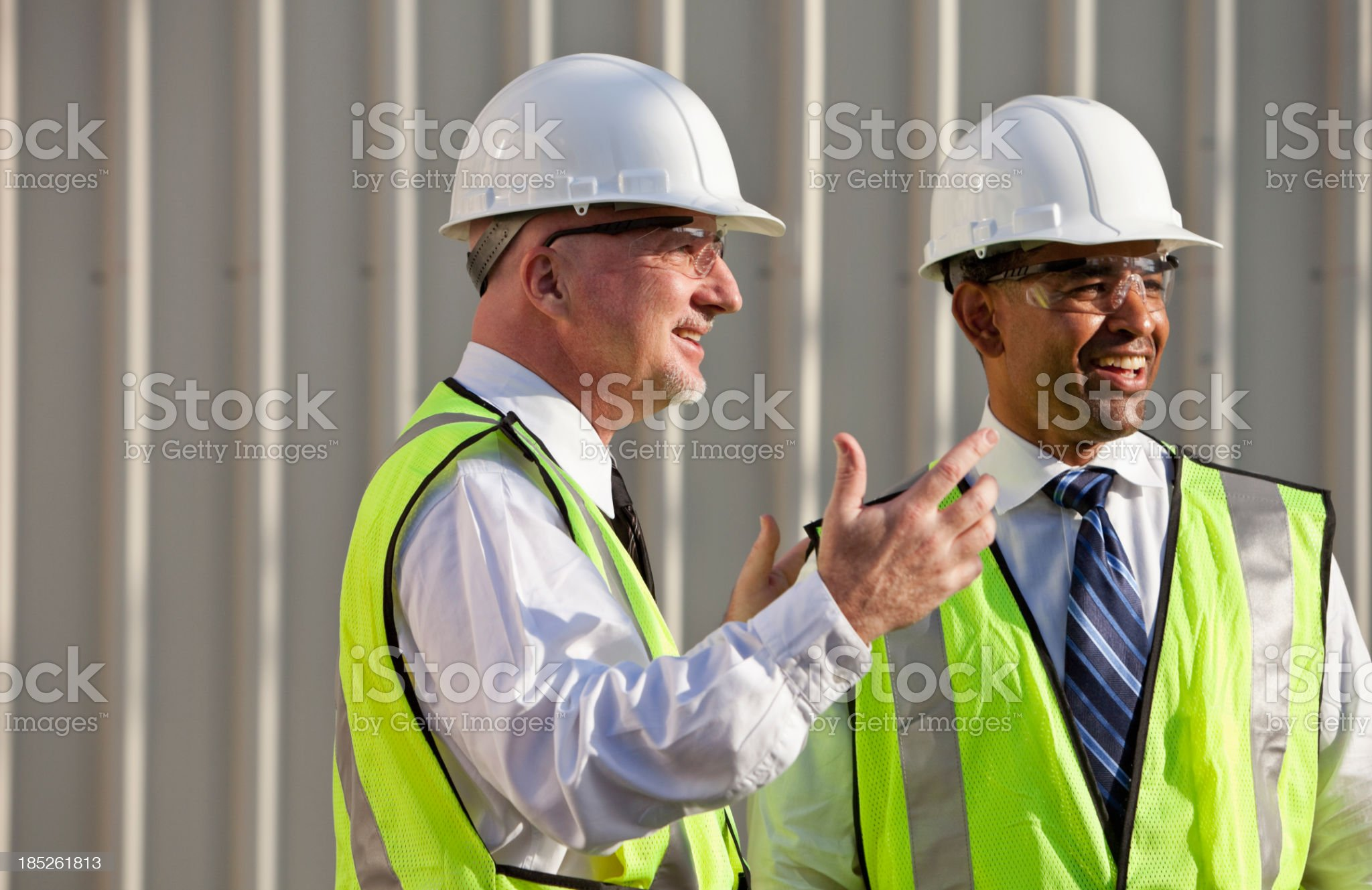 Engineers wearing safety vests having conversation royalty-free stock photo