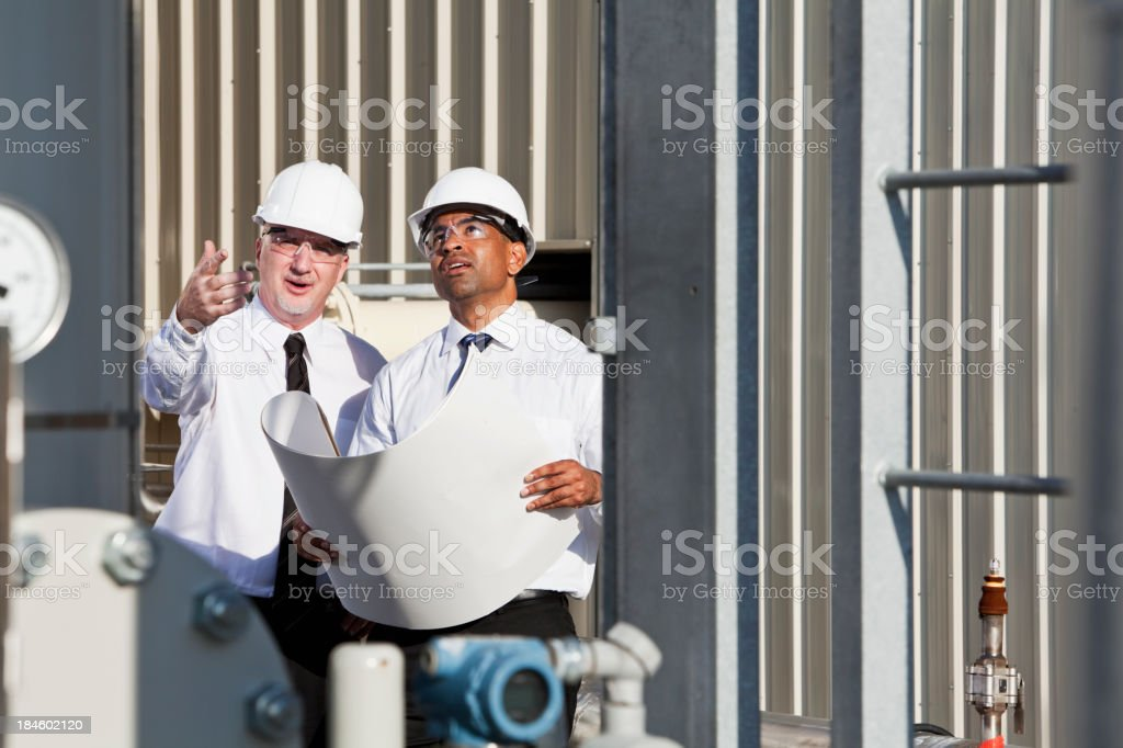 Engineers with plans at job site royalty-free stock photo