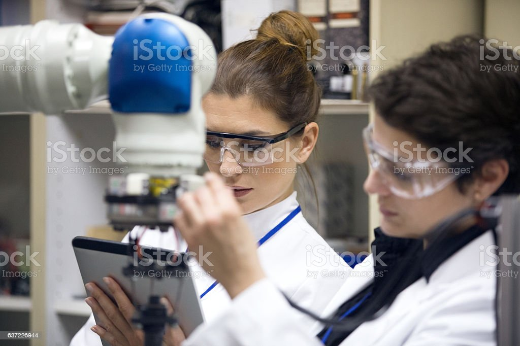 Engineers working with robotic arm stock photo