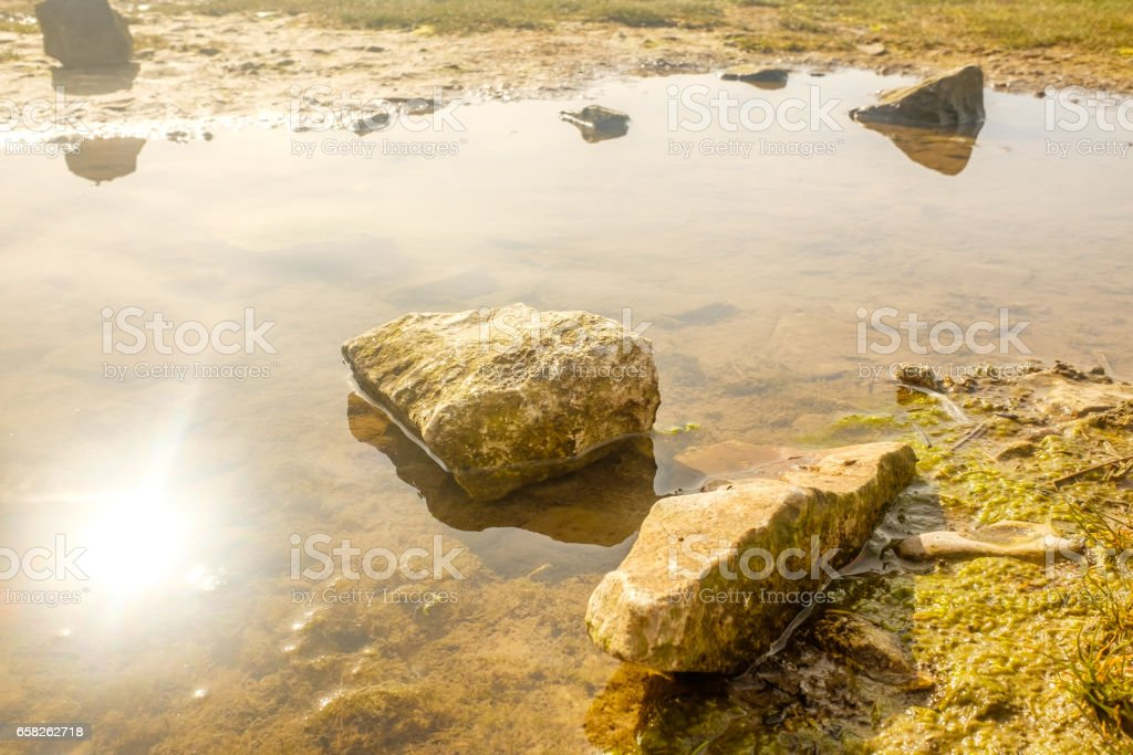 England, UK on a spring morning. Rocks and pools on sandy beach. stock photo