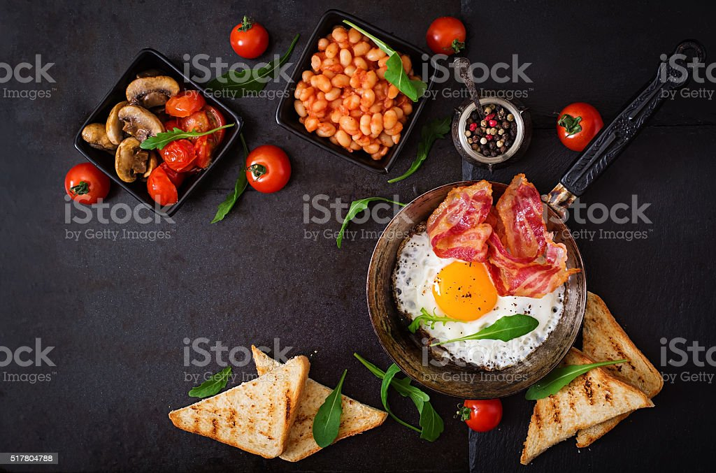 English breakfast - fried egg, beans, tomatoes, bacon and toast. stock photo