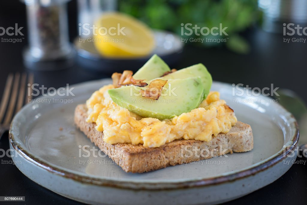 English breakfast with scrambled eggs, avocado slices and roasted bacon stock photo