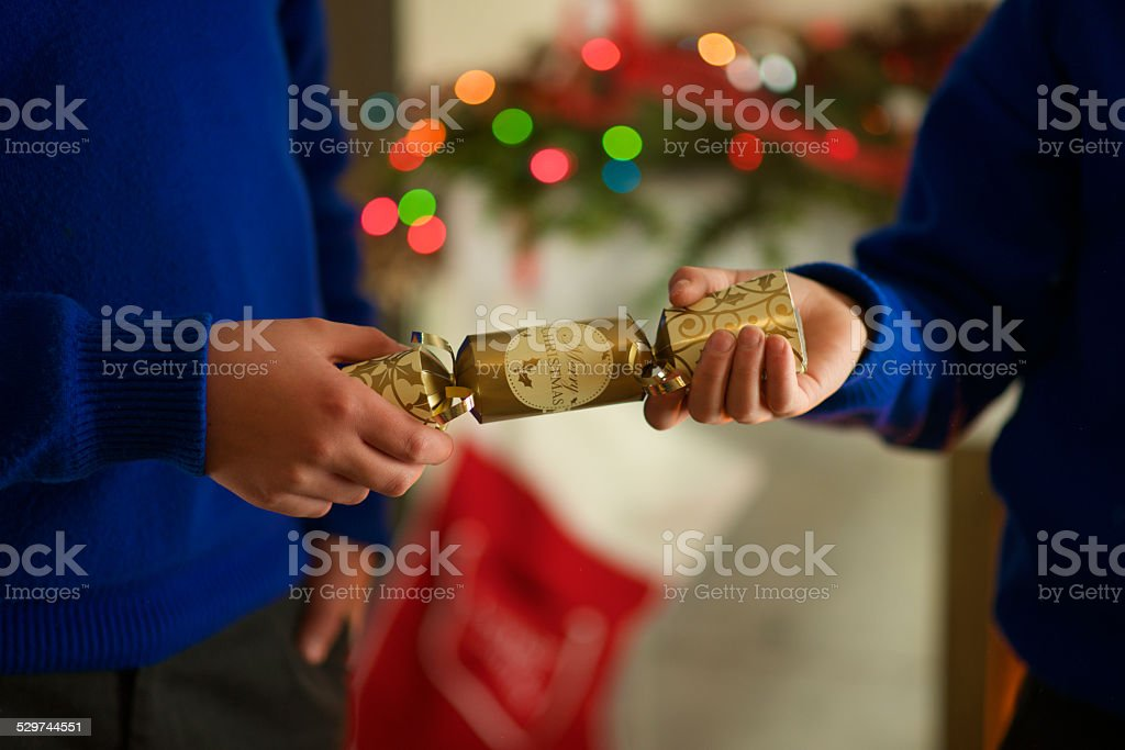 English Christmas Cracker pulled by two Kids stock photo