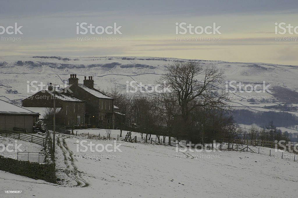 English farmhouse in the winter snow evening light, Yorkshire royalty-free stock photo