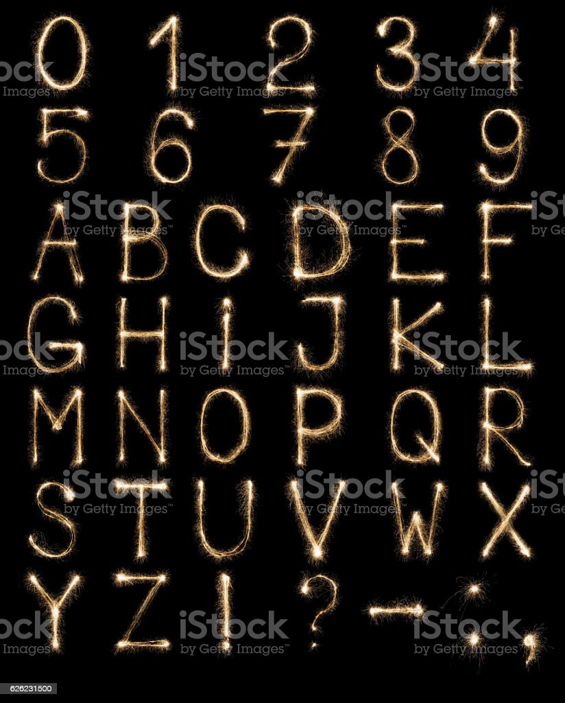 English Letters from sparklers, alphabet and numbers on black background. stock photo