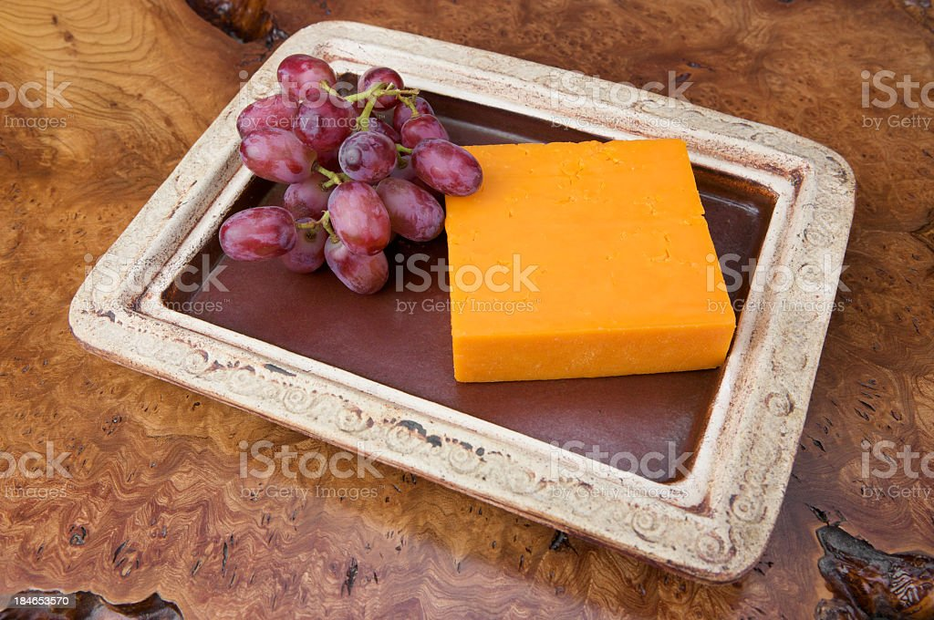 English Red Leicester cheese and red grapes on rustic plate stock photo