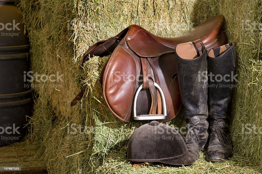 English riding tack on a barn corner next to hay stock photo