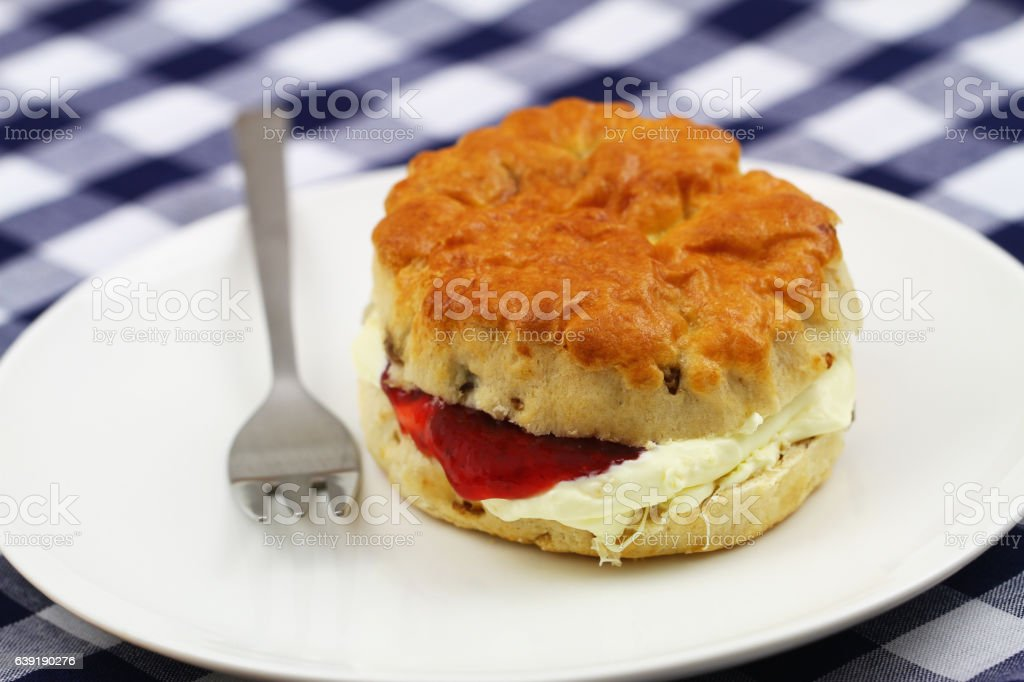 English scone with raisins with traditional clotted cream, strawberry jam stock photo