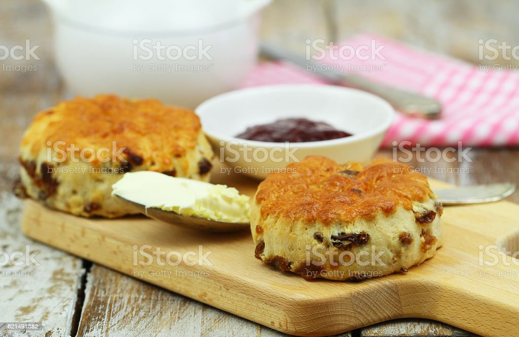 English scones with raisins on wooden board, clotted cream, jam stock photo