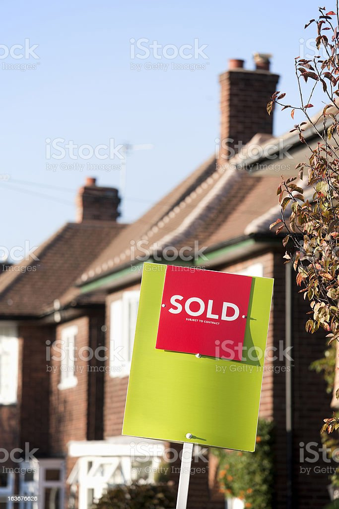 English suburban house with a 'SOLD' sign outside. royalty-free stock photo
