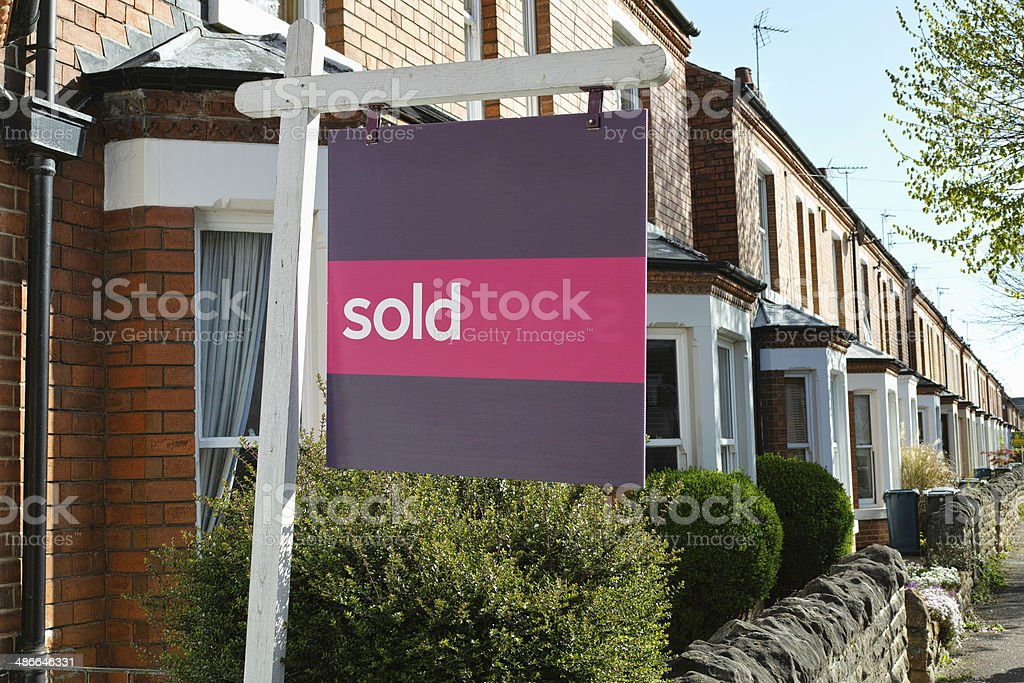 English suburban house with 'sold' sign. stock photo