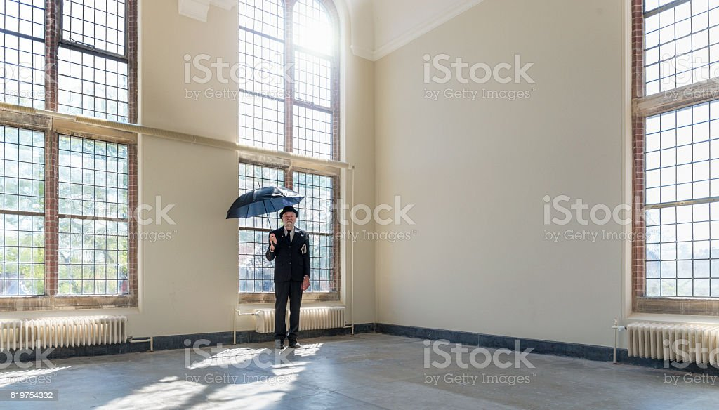 Englishman in bowler hat and open black umbrella. stock photo
