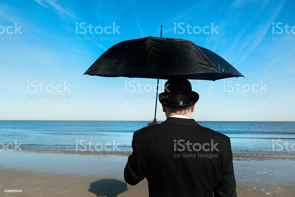 Englishman standing on the beach, overlooking the sea stock photo