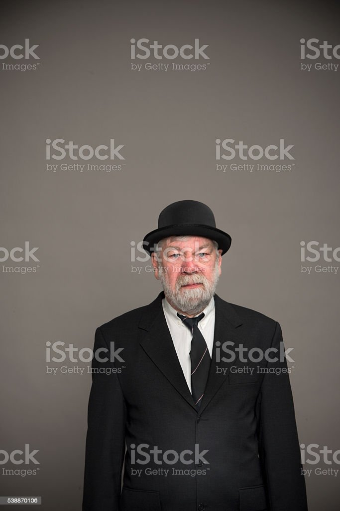 Englishman with bowler hat against gray stock photo