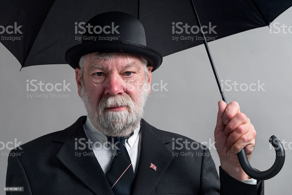 Englishman with bowler hat and open black umbrella. stock photo