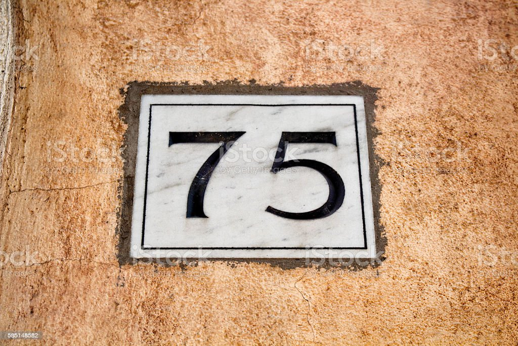Engraved old building number 75 in Rome stock photo