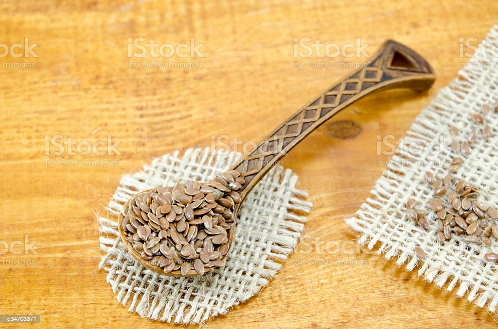 Engraved wooden spoon filled with linseeds royalty-free stock photo