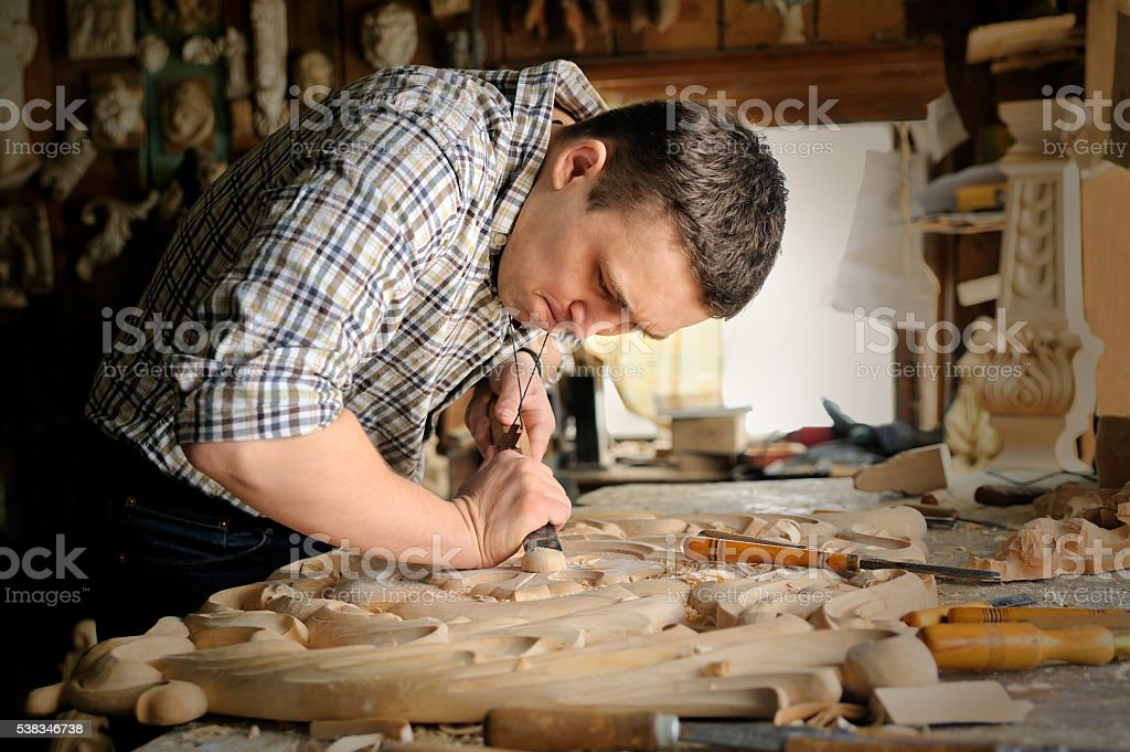 Engraver, shot of a male carpenter working in his workshop stock photo