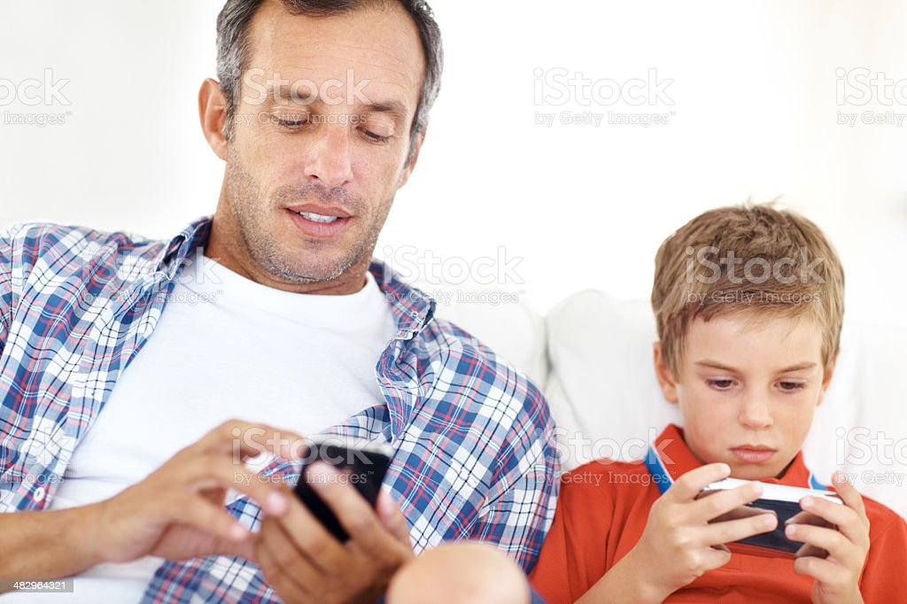 Engrossed in their new toys! - Father & Son royalty-free stock photo
