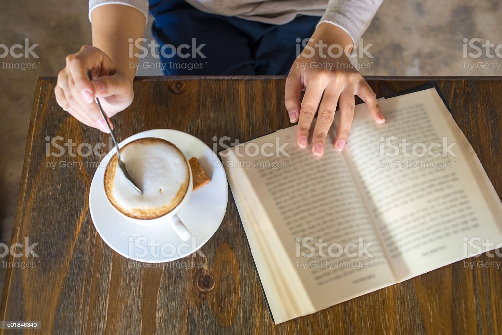 Enjoy a free day with book and cup of cappuccino stock photo