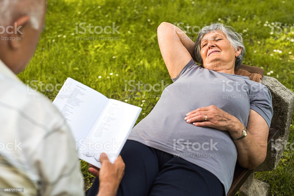 I enjoy listening him reading a book to me! stock photo