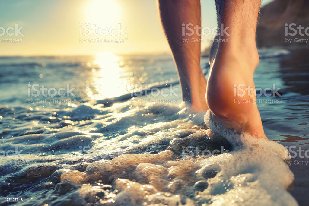 Enjoying a barefooted walk at the ocean stock photo