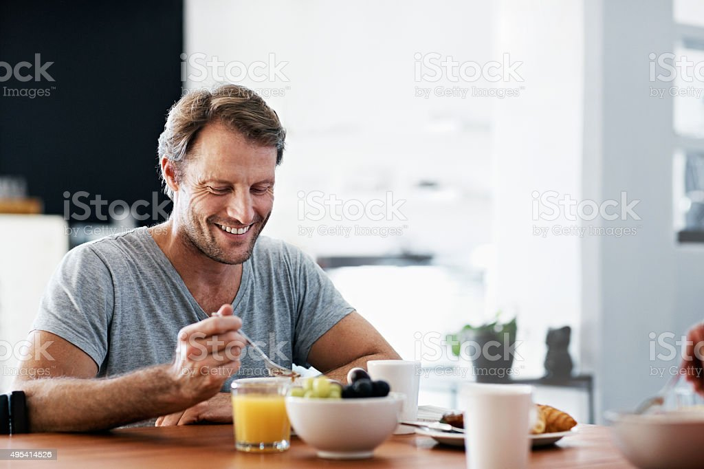Shot of a man eating breakfast at the dining table