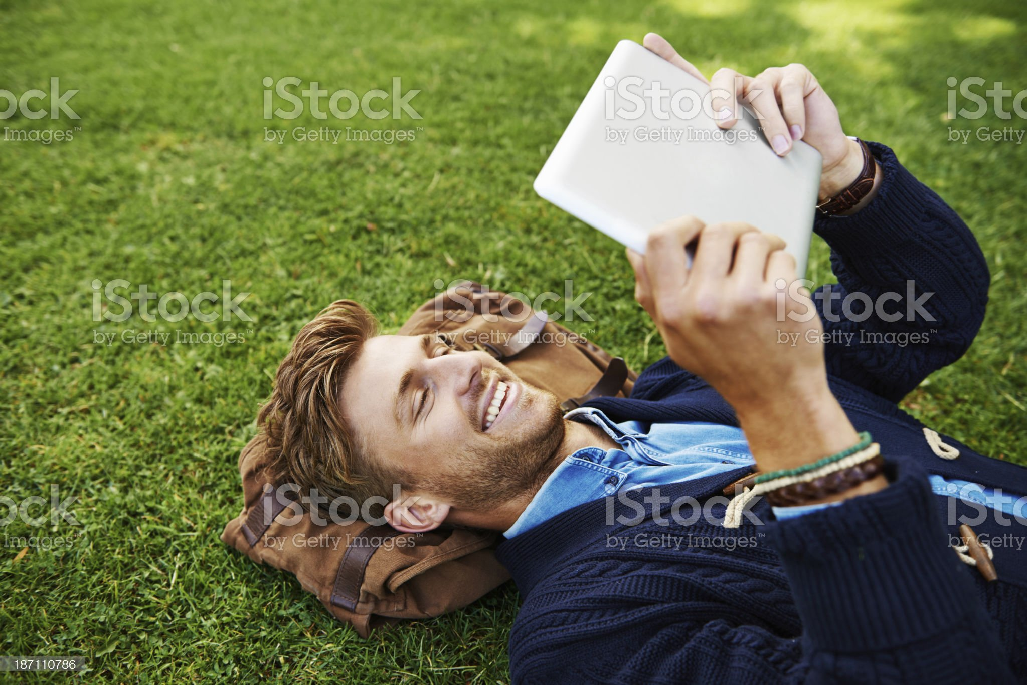 Enjoying an eBook in the local park royalty-free stock photo