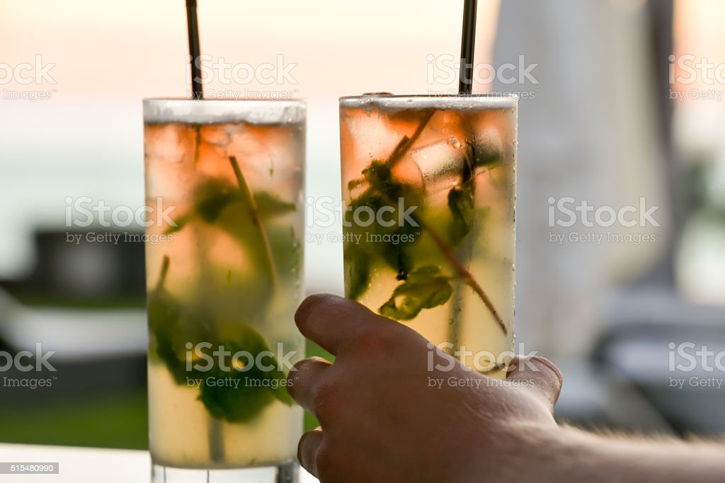 enjoying cocktails at sunset with your lovely wife, husband, friend stock photo