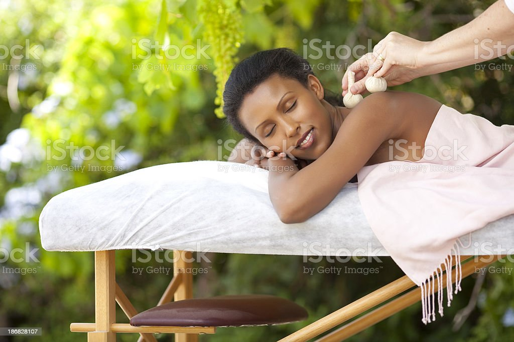 Enjoying massage with Thai herbal sacks. stock photo
