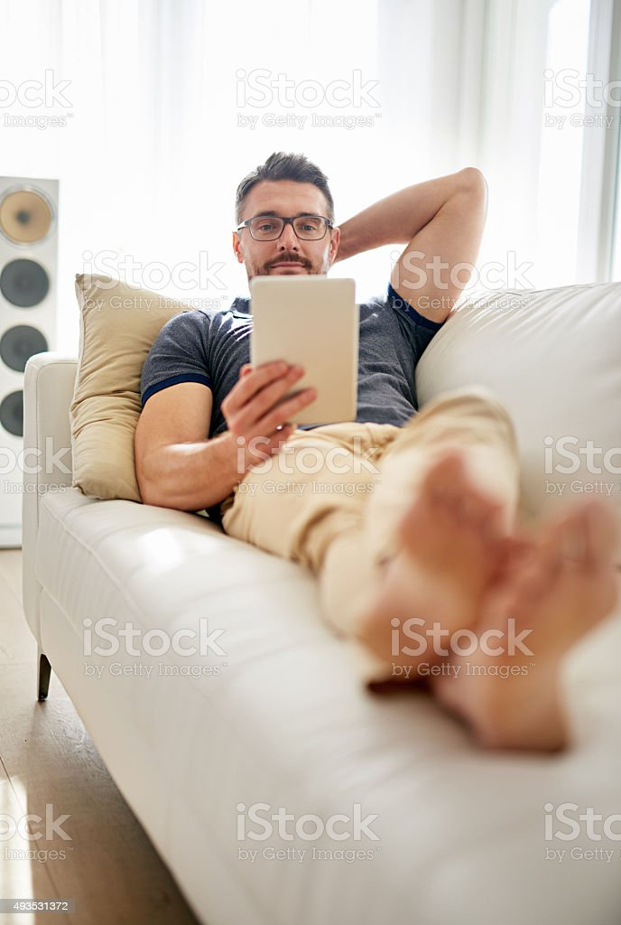 Enjoying some downtime with his digital tablet stock photo