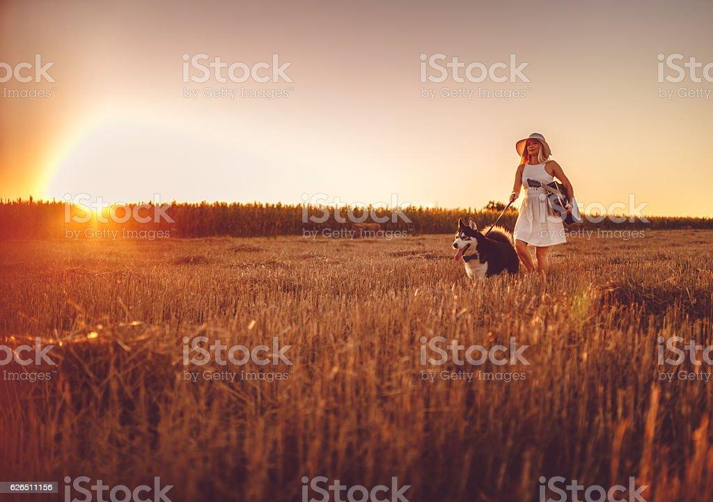 Enjoying sunset with dog and guitar stock photo