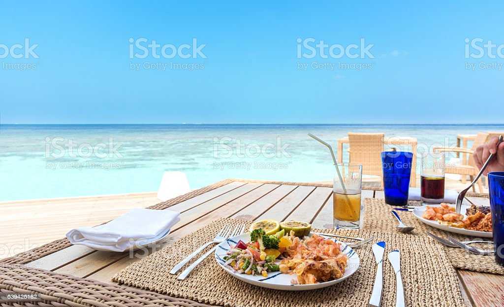 Enjoying tasty breakfast beside the tropical sea stock photo