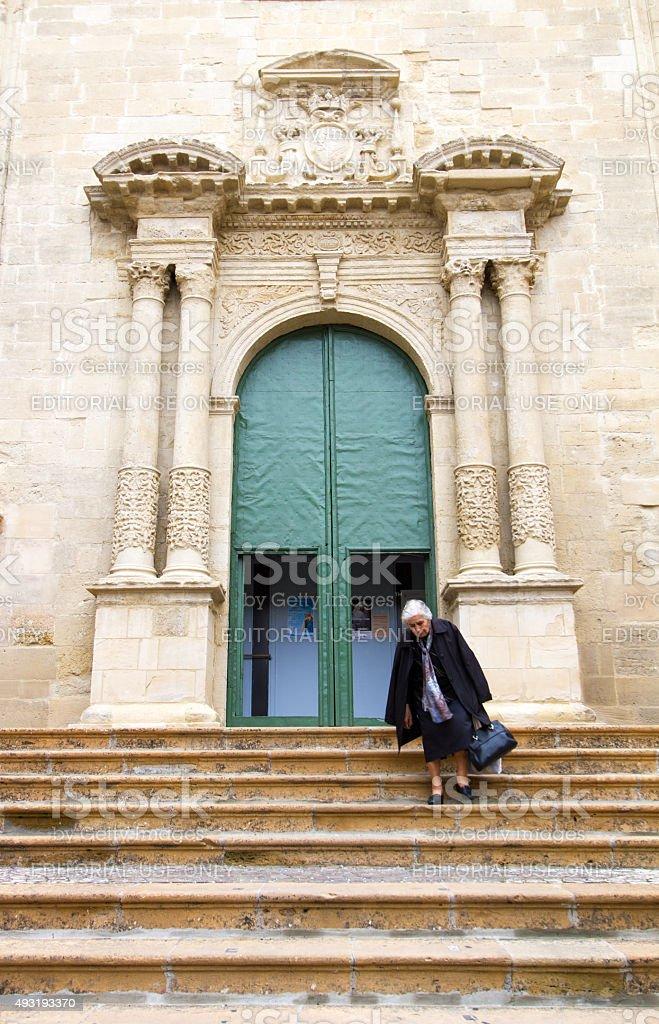 Enna, Sicily: Senior Woman Descending Steps of Ornate Church stock photo