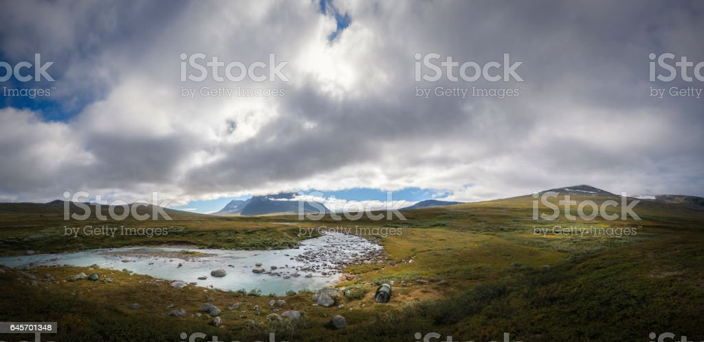 Enormous landscape panorama of Sarek with Sami shelter and tents on river bank trekking in Sweden stock photo