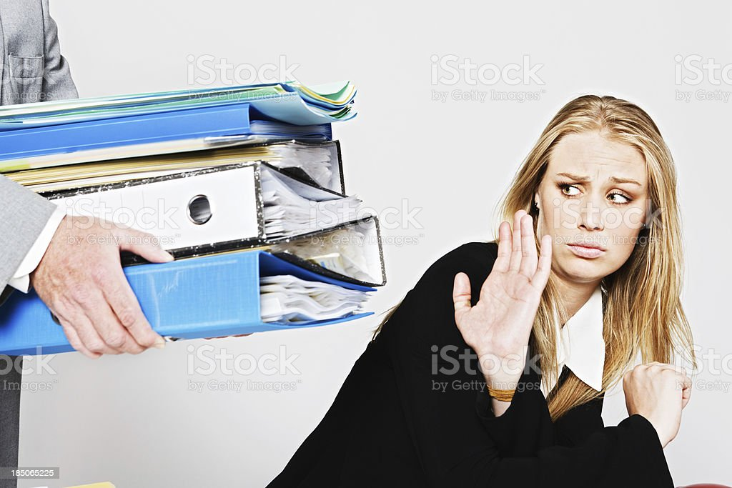 Enough already: businesswoman refuses extra work being handed over stock photo