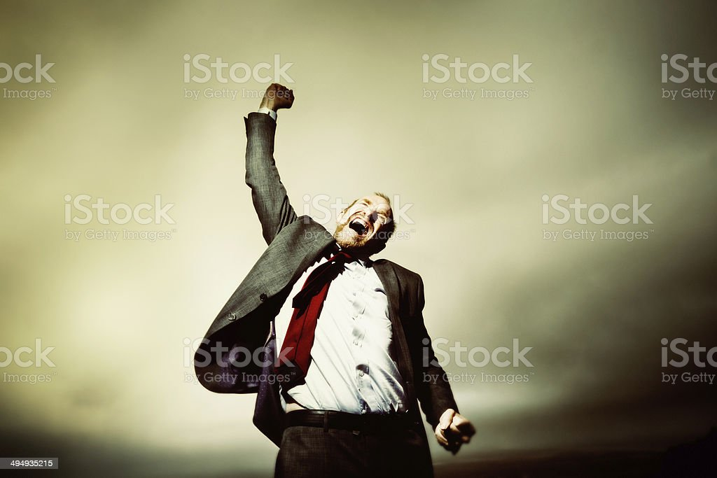 Enough! Distraught businessman rages against fate on mountain top stock photo